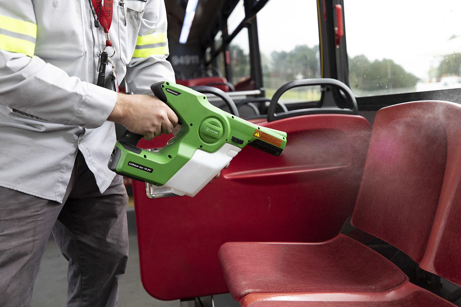 Photo of a sanitation sprayer spraying mist on a bus seat.
