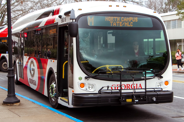 UGA electric bus at a bus stop.